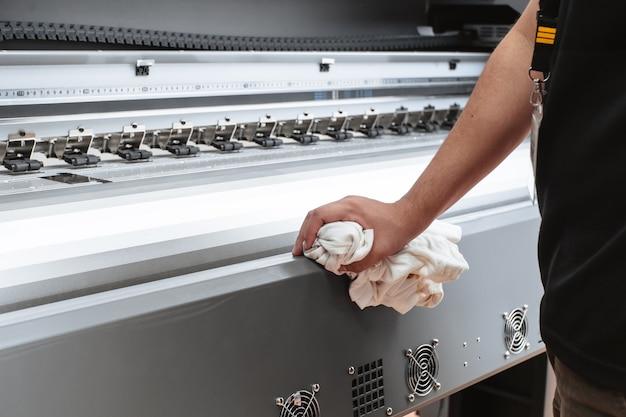 Pessoa que limpa uma plotadora de impressão. as mãos limpam a máquina de grande formato.