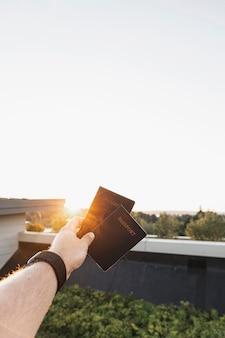 Pessoa que mostra os passaportes no pôr do sol