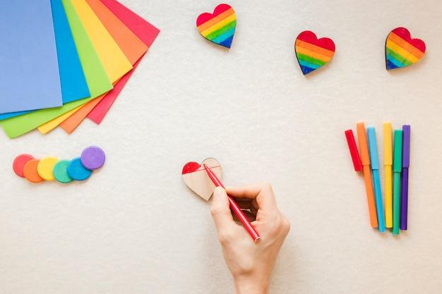 Pessoa que pinta o coração do arco-íris com caneta de feltro vermelho