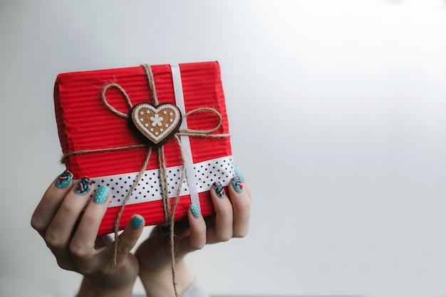 Pessoa que prende o presente vermelho com um coração de ouro com uma estrela no centro