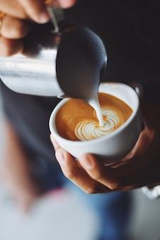 Pessoa que serve uma xícara de café