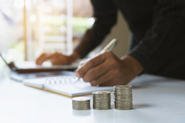 Pessoa que trabalha e que escreve no caderno com a pilha de moedas para o conceito financeiro e de contabilidade.
