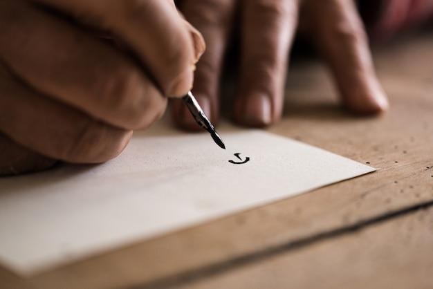 Pessoa que usa caneta e tinta para fazer caligrafia