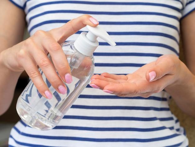 Pessoa que usa desinfetante para as mãos de garrafa de plástico