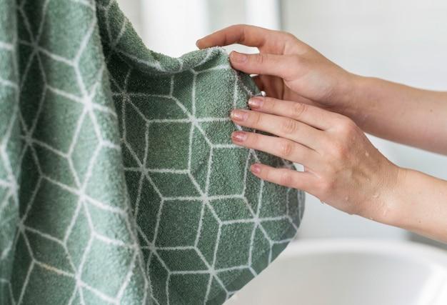 Pessoa que usa toalha para secar as mãos