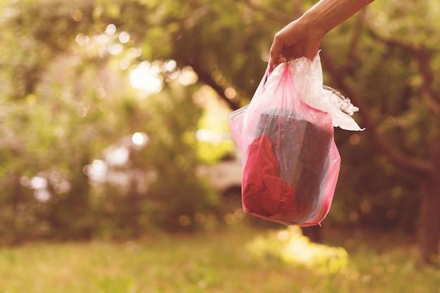 Pessoa recolhe o pacote e leva o lixo para fora, cuida da natureza e do parque