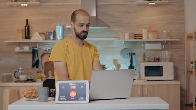 Pessoa remota trabalhando em uma casa moderna dando comando de voz para tablet com aplicativo de casa inteligente e luzes acesas