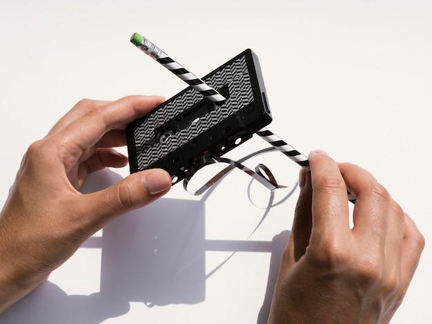 Pessoa reparando fita cassete preta com lápis