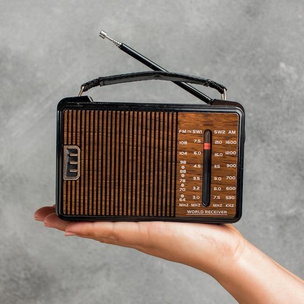 Pessoa segurando a vista frontal de um rádio vintage