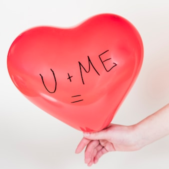 Pessoa segurando balão de coração com u + me = inscrição