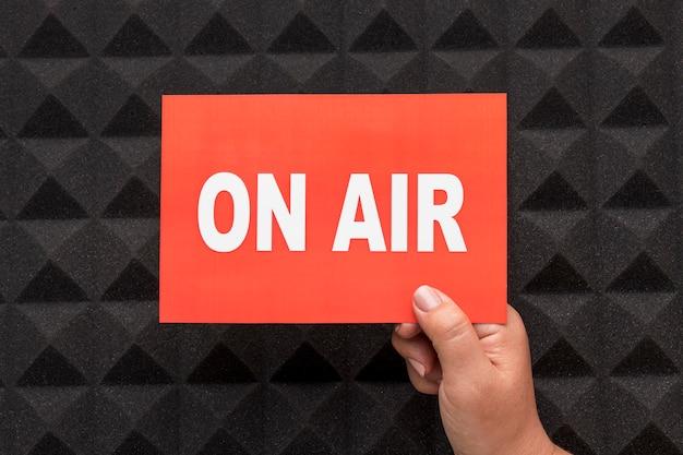 Pessoa segurando banner de rádio de transmissão ao vivo