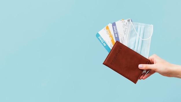 Pessoa segurando bilhetes de avião e passaporte com espaço de cópia