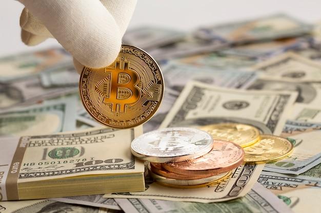 Pessoa segurando bitcoin nos dedos