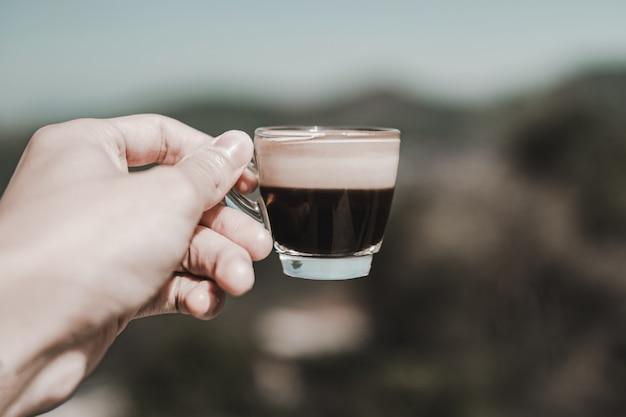 Pessoa segurando café americano quente em um copo colocado com luz do sol pela manhã