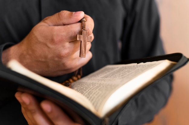 Pessoa, segurando, livro sagrado e rosário