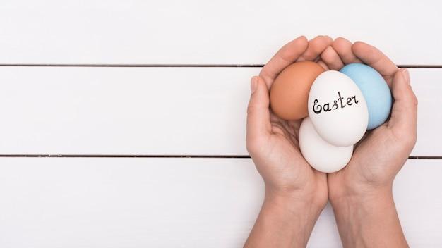 Pessoa segurando ovos coloridos com inscrição de páscoa