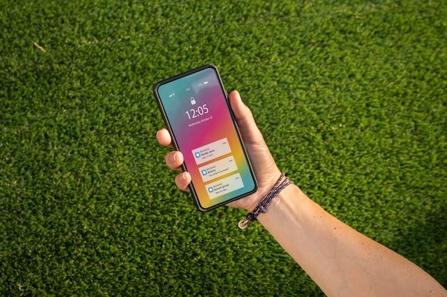 Pessoa segurando seu smartphone com um aplicativo na tela