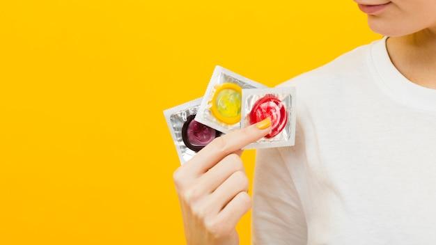 Pessoa, segurando, três, preservativos diferentes, com, espaço cópia