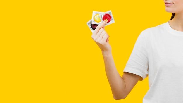Pessoa segurando três preservativos diferentes