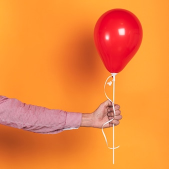 Pessoa, segurando um balão vermelho em fundo laranja