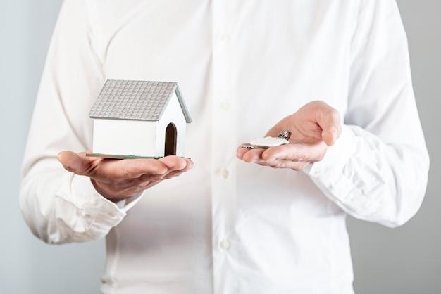 Pessoa, segurando um brinquedo de casa e chaves