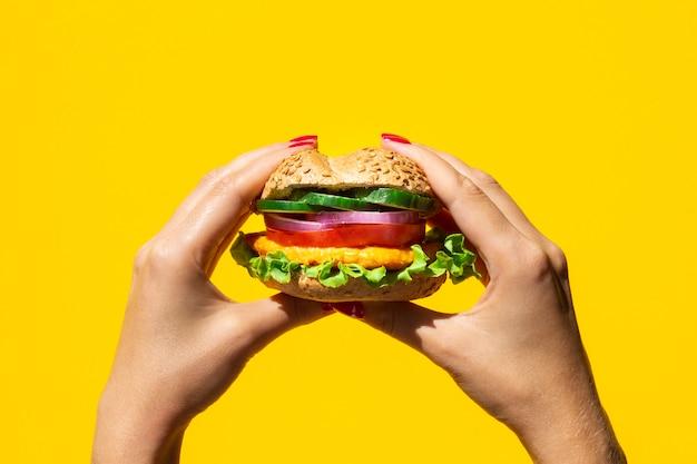 Pessoa, segurando um delicioso hambúrguer vegetariano