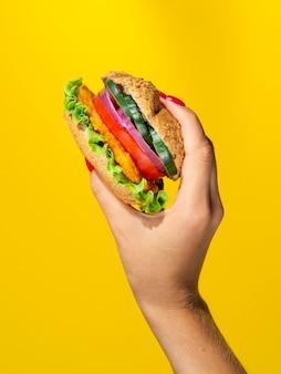 Pessoa, segurando um hambúrguer vegetariano suculento