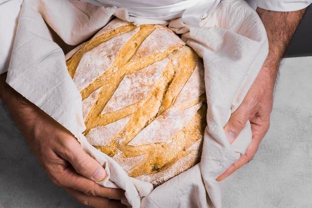 Pessoa, segurando um pão embrulhado