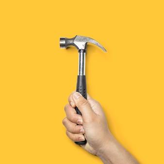 Pessoa segurando um pequeno martelo com um cabo preto, o martelo é uma ferramenta para pregos de martelo, isolados em um fundo amarelo e traçado de recorte.