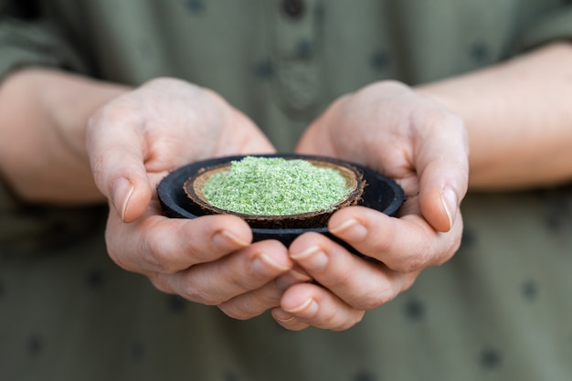 Pessoa segurando um prato de pó verde usado para alimentos veganos crus