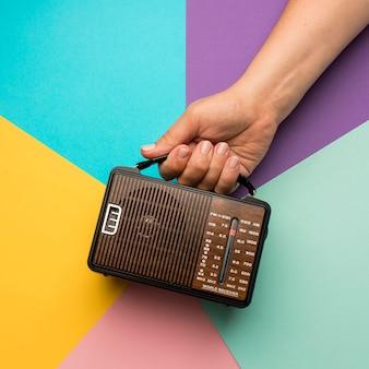 Pessoa segurando um receptor de rádio de transmissão retrô