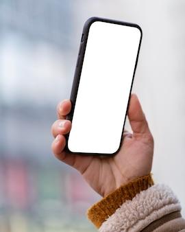 Pessoa segurando um smartphone com tela vazia