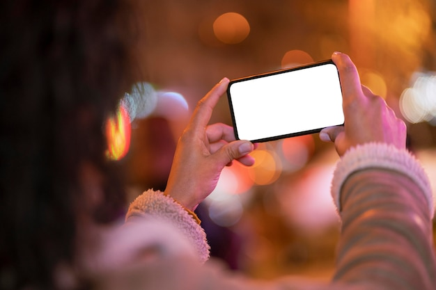 Pessoa segurando um smartphone em branco com efeito bokeh ao redor