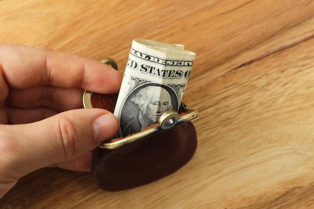 Pessoa segurando uma bolsa de moedas com algum dinheiro dentro sobre uma superfície de madeira