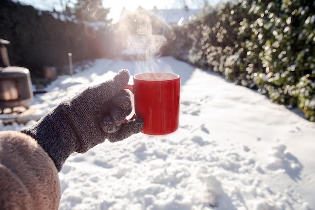 Pessoa segurando uma caneca vermelha com café quente, fumaça fumegante e luvas na neve