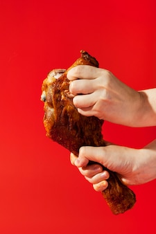 Pessoa segurando uma coxa de frango e quebrando um pedaço dela