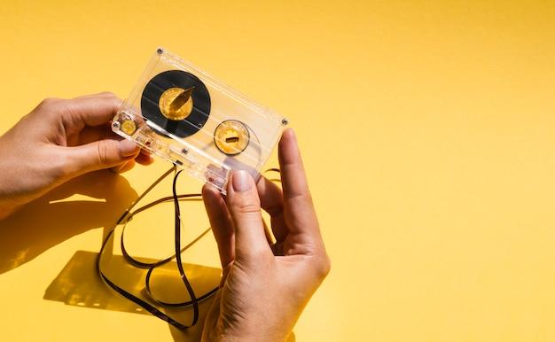 Pessoa, segurando uma fita cassete quebrada com cópia-espaço