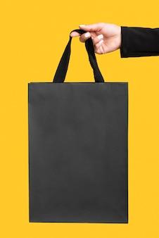 Pessoa segurando uma grande sacola de compras preta