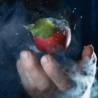 Pessoa, segurando uma maçã vermelha com gotas de água