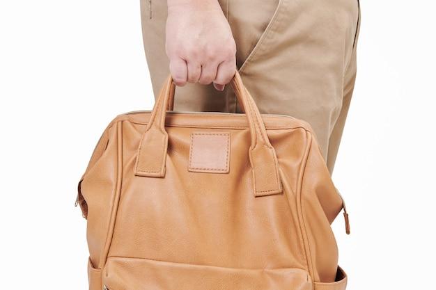 Pessoa segurando uma mochila de couro marrom