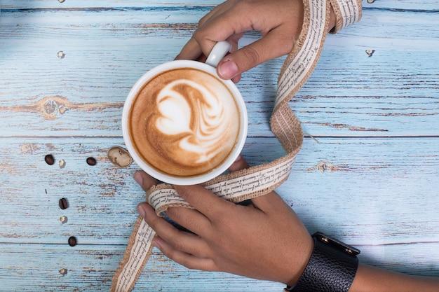 Pessoa segurando uma xícara de café com leite com as duas mãos