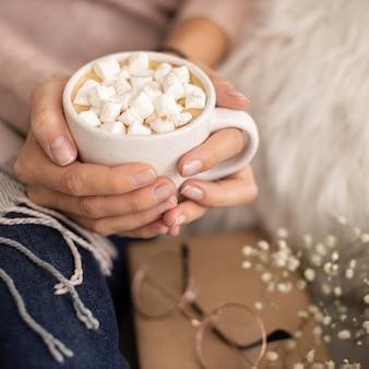 Pessoa segurando uma xícara de chocolate quente com marshmallows