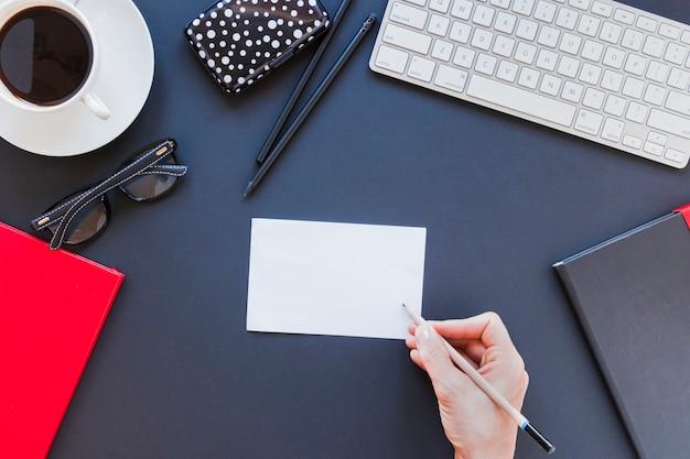 Pessoa sem rosto, escrevendo na nota perto de artigos de papelaria e teclado na mesa com uma xícara de café