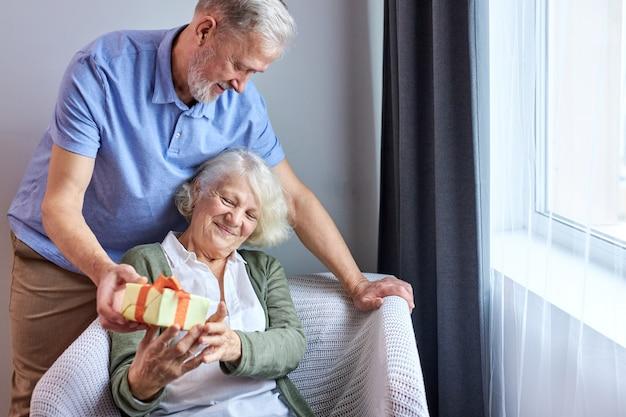 Pessoa sênior do sexo feminino com rosto satisfeito recebendo uma caixa de presentes com seu belo marido, um casal de idosos grisalhos comemorando o aniversário de uma mulher, um homem a parabeniza