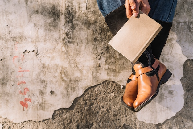 Pessoa sentada, mãos, segurando, livro fechado