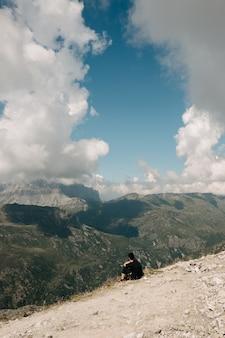 Pessoa sentada na beira de uma montanha rochosa
