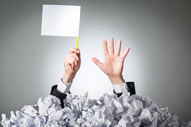 Pessoa sob a pilha de papéis amassados com a mão segurando uma placa de desistência