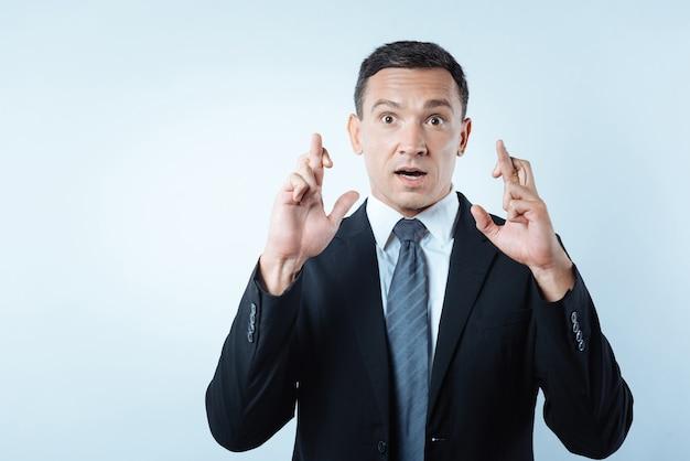 Pessoa supersticiosa. homem bonito e agradável olhando para você e cruzando os dedos enquanto acredita em superstições