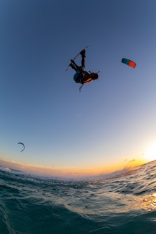 Pessoa surfando e pilotando um pára-quedas ao mesmo tempo no kitesurf