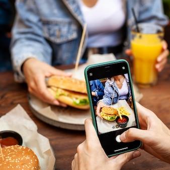 Pessoa tirando foto de alguém comendo hambúrguer